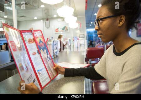 African American girl teen in a diner reading a menu, eating, drinking a milkshake and playing music on the jukebox. - Stock Photo