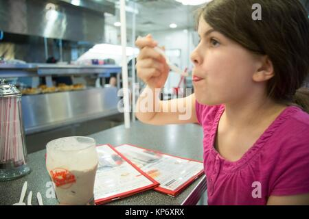 Pre-teen and teen in a diner reading a menu , eating, drinking a milkshake and playing music on the jukebox. - Stock Photo