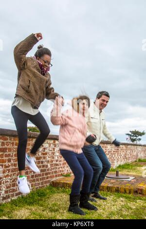handsome dark hair Dad in his 40´s, 45´s and his girls, one african american teen and one caucasian pre teen, jumping - Stock Photo
