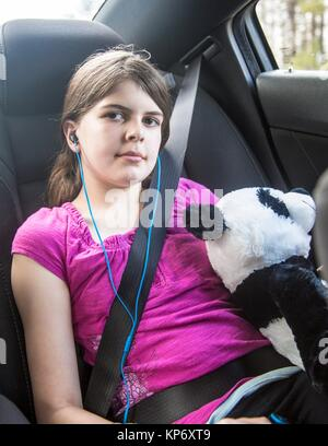 one caucasian preteen 11 years old in the car with her sit beat on and resting with oversized panda stuff animals. - Stock Photo