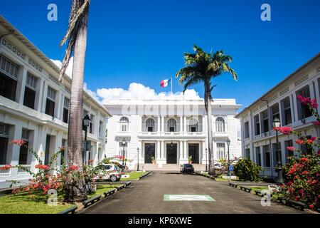 Gorgeous city hall with while column Louis Blanc with palm trees and park entrance in Fort de France, Martinique. - Stock Photo