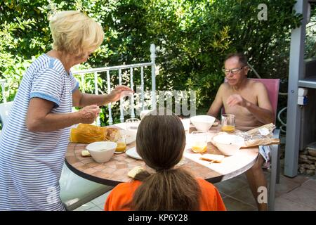 Caucasian family outside about to have breakfast outdoor. Grandparents are in their 60´s and their granddaughter - Stock Photo