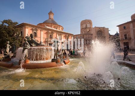Turia fountain with the Virgen de los Desamparados Basilica and Santa Maria del Mar Cathedral on the back Plaza - Stock Photo
