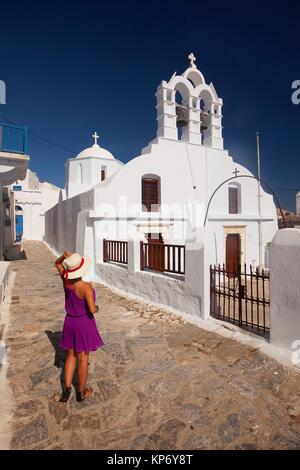 Tourist woman standing in front of the whitewashed Orthodox church in the old town Chora or Chorio, Amorgos, Cyclades - Stock Photo