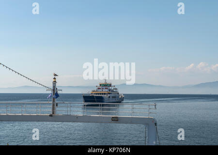 Ferry boat in the sea with passengers on board, back view - Stock Photo