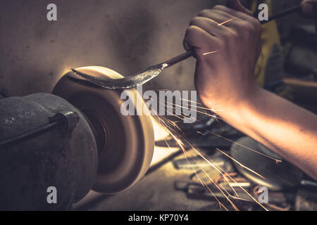 Working  process of metal handling with sparks in metal workshop on special equipment - Stock Photo