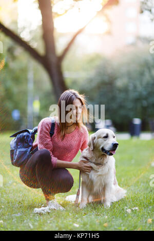 Picture of brunette with backpack on walk with retriever - Stock Photo