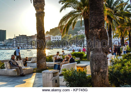 Afternoon at the Riva Promenade at the harbor of Split Croatia as tourists enjoy watching boats at sea and relax - Stock Photo