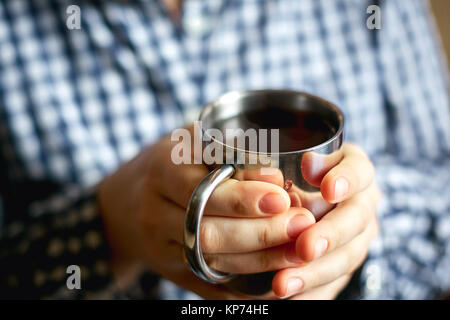 a young woman sits by the window and holds a mug with hot tea - Stock Photo