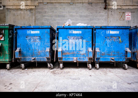 Municipal blue waste collection garbage dumpsters, wheelie bins, in an alleyway in downtown Toronto, Ontario, Canada. - Stock Photo