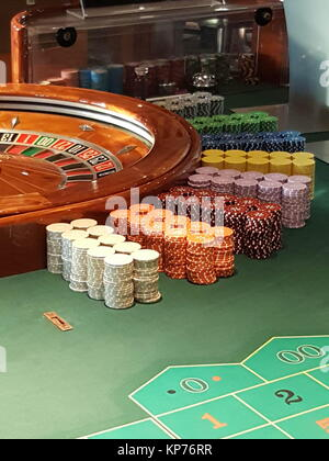Roulette wheel and chips on a casino table - Stock Photo