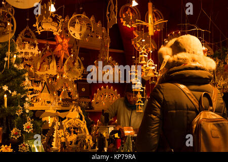 Christmas market in Basel, Switzerland. 9th of December 2017. A woman is buying traditional wooden christmas decorations - Stock Photo