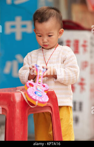 GUANGZHOU-DEC. 13, 2009. Young Chinese boy with a toy. Birth rates in China rose to their highest level as a result - Stock Photo