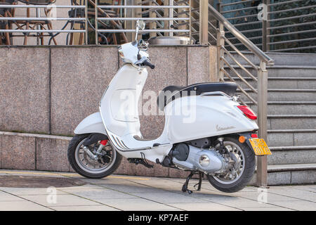 YIWU-JAN. 15, 2016. White Vespa scooter parked in front of a café. Vespa is an Italian scooter brand manufactured - Stock Photo