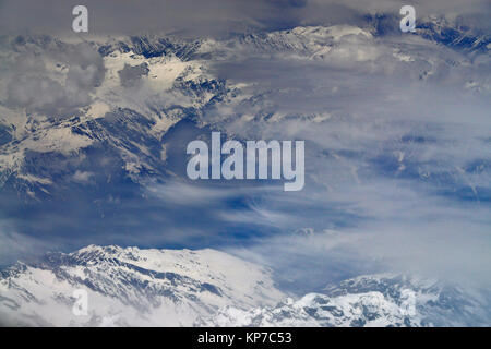 High snowy mountains, taken from an airplane, the peaks are covered with fog and clouds, winter in the Himalayas. - Stock Photo