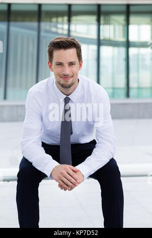 Businessman sitting on the blench - Stock Photo