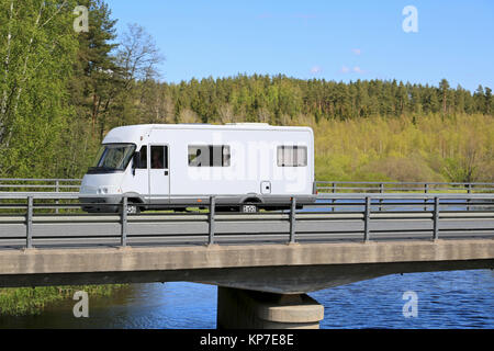 White motorhome traveling along scenic road on a bridge over water at summer. - Stock Photo