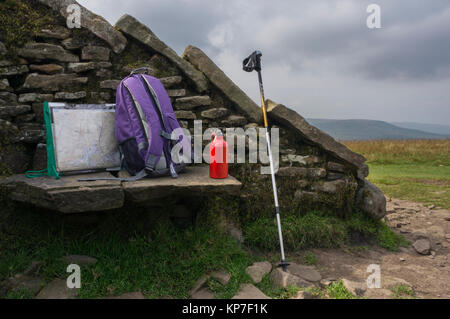 Stone windbreak shelter & seat on summit of Whernside, with map in holder, rucksack,red  water bottle & trekking - Stock Photo
