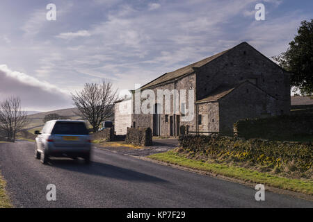 Car (Land Rover Freelander) travelling past stone, roadside barn & farm buildings on country road - Barden, Yorkshire - Stock Photo