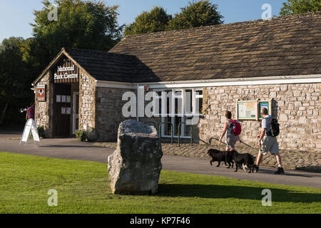 Sunny, autumn day, exterior view of National Park Visitor Centre, with couple of walkers & 2 dogs, passing - Malham, - Stock Photo