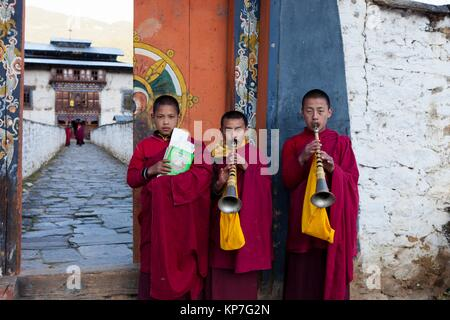 Novice monks with flutes (Rgya-Gling) outside the temple of Wangdichholing Palace built in 1857 as the Kingdom´s - Stock Photo