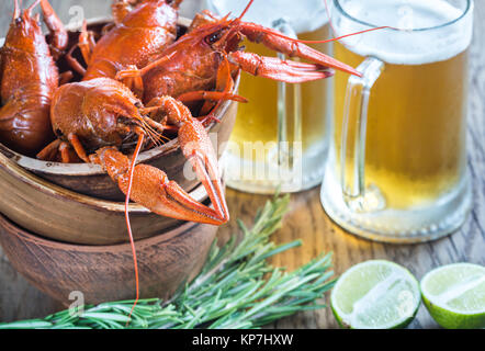 Bowl of boiled crayfish with two mugs of beer - Stock Photo