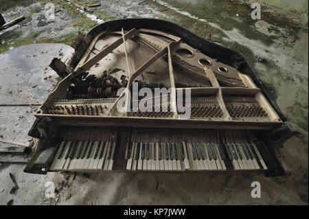 Old ruined grand piano in the concert hall in the house of culture Pripyat, no covers, the keys are covered with - Stock Photo
