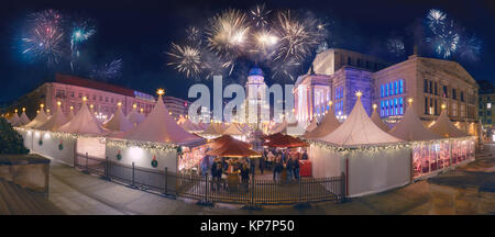 Berlin on New Year's Eve. Fireworks over Iluminated Christmas market at Gandarmenmarkt. Panoramic toned image. - Stock Photo