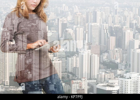 double exposure of woman using tablet technology and urban build - Stock Photo