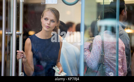 Pretty, young woman leaving a store/restaurant with cash in her hand after having paid for for the goods/food - Stock Photo