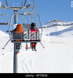Two skiers go up on chair-lift and snowy ski slope at sun winter day. Caucasus Mountains, Georgia, region Gudauri. - Stock Photo