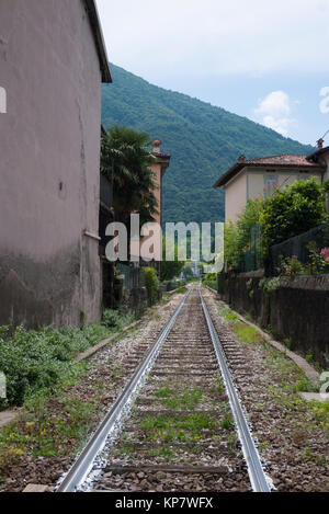 Railway tracks running through the centre of Pisogne, a small town in Italy by Lake Iseo - Stock Photo