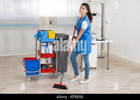 Happy Female Janitor Cleaning Floor With Broom In Office - Stock Photo