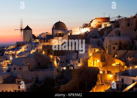 View to the windmill, church and Cyclades houses in Oia village after the sunset, Santorini, Cyclades Islands, Greek - Stock Photo