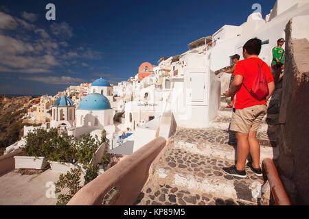 Tourists taking photos of the blue domed churches in Oia village, Santorini, Cyclades Islands, Greek Islands, Greece, - Stock Photo