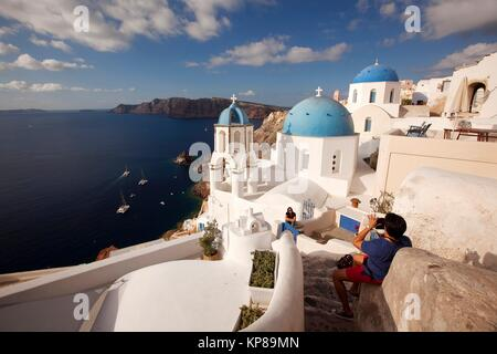 Tourists taking photos in front of the blue domed churches in Oia village, Santorini, Cyclades Islands, Greek Islands, - Stock Photo