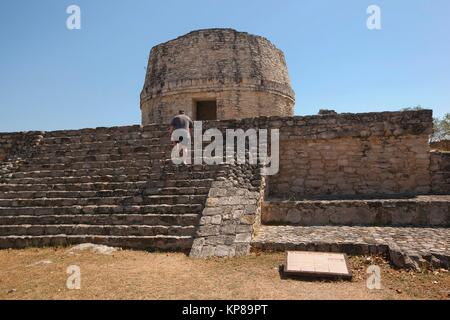 Tourist climbing up the stairs to the Templo Redondo-Round Temple in Mayapan Archeological site, Merida, Yucatan - Stock Photo