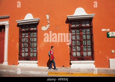 Young man walking in the street at the historic center in front of colonial buildings, Campeche, Campeche State, - Stock Photo