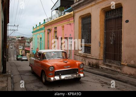 Old American car used as shared taxi at the street in front of the colonial buildings, Santiago de Cuba, Cuba, Central - Stock Photo