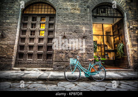 Blue bicycle on cobblestone street in Florence, Italy - Stock Photo