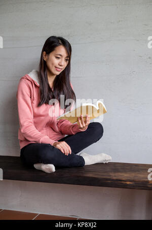 Asian Woman reading book at home - Stock Photo