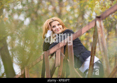 Young beautiful girl standing on the bridge, leaning on the railing and looking pensively into the distance - Stock Photo