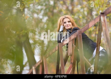 Young beautiful girl standing on the bridge and happily leaning on the railing - Stock Photo