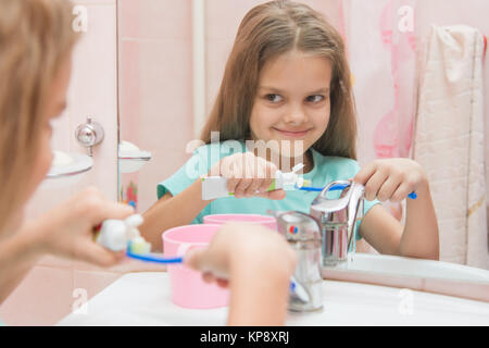 Happy little girl squeezes the toothpaste from a tube on toothbrush - Stock Photo