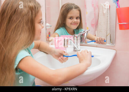 The girl washes a toothbrush under the tap - Stock Photo