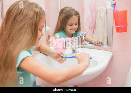 Girl rinse the toothbrush under running tap water - Stock Photo