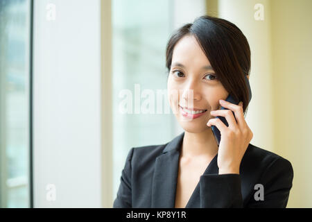 Businesswoman talk to cellphone at office - Stock Photo