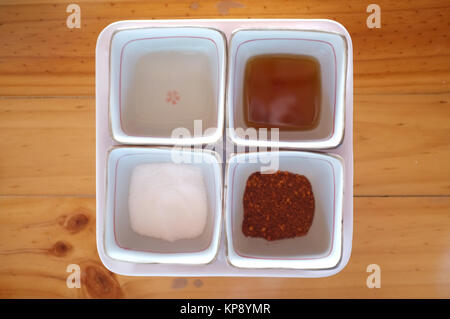 Seasoning container include cayenne pepper, sugar, fish sauce and chilies in vinegar - Stock Photo