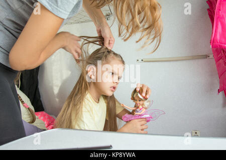 Mom tries to unravel the tangled hair girl in a train - Stock Photo