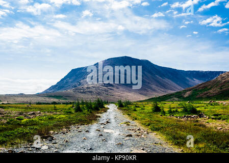 Rocky gravel path leading to mountain under clouds and sky - Stock Photo
